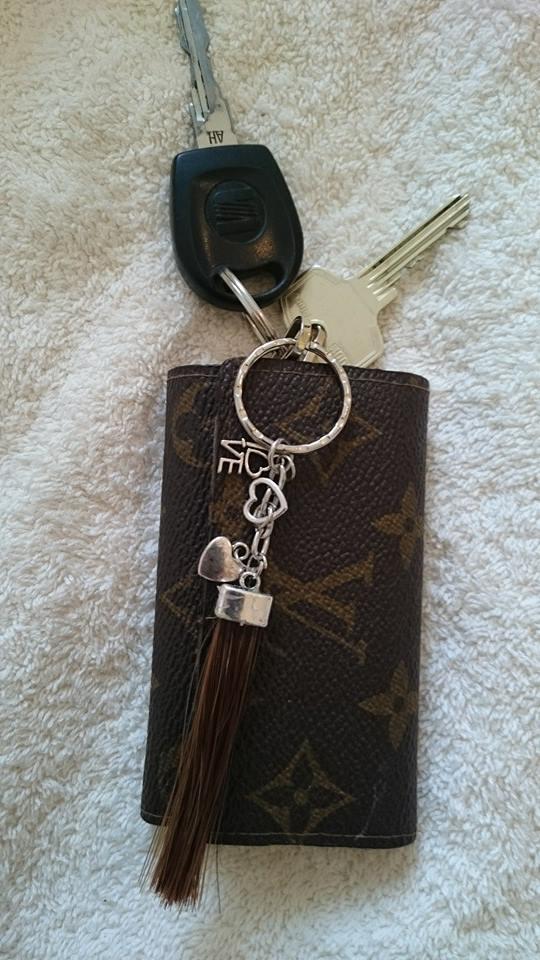 Sleutelhanger van ilion zijn haar aan een Louis Vuitton pochete